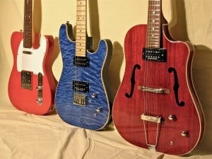 Three custom, hand-built guitars in finished pose side by side.
